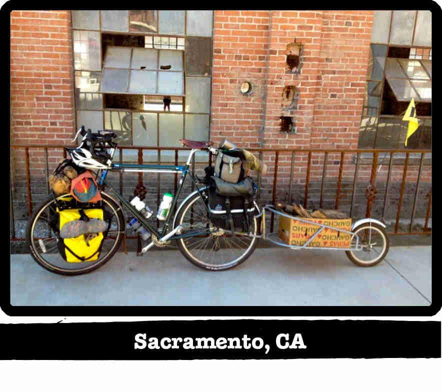 Left side view of a green Surly Long Haul Trucker bike, loaded with gear,on a side walk - Sacramento, CA tag below image