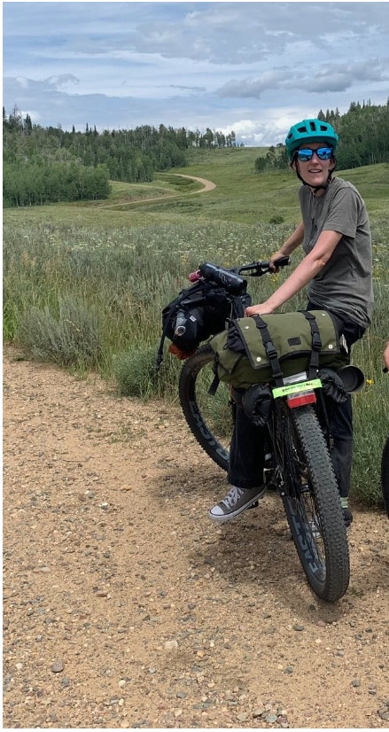 Cyclist on the side of a gravel road on a black Surly ECR bike loaded with gear in a hilly prairie with trees behind