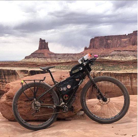 Right side view of a black Surly ECR bike loaded with gear leaning  on a large rock on the edge of a desert canyon