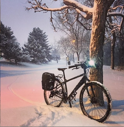 A black Surly ECR bike with headlight on sits against a tree at night in a snow covered field with pine trees behind it
