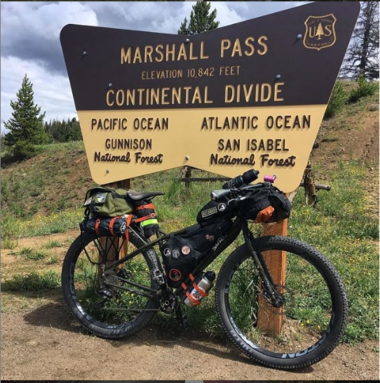 Right side view of a black Surly ECR bike loaded with gear leans on a Marshall Pass Continental divide sign