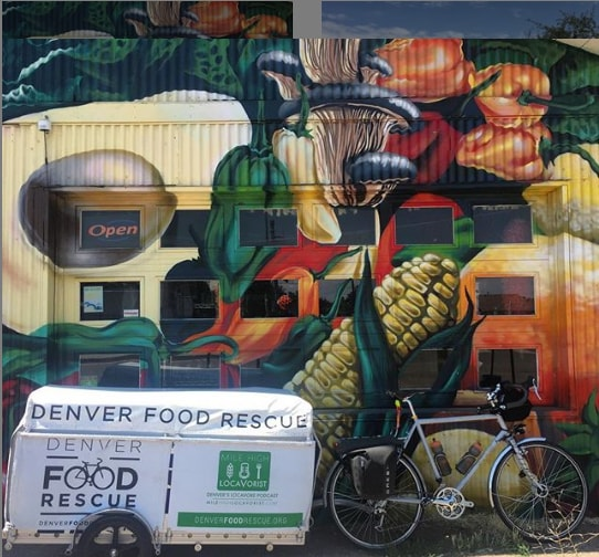 A bike with and a Denver Food Rescue trailer behind it is parked aside steel building painted in colorful vegetables