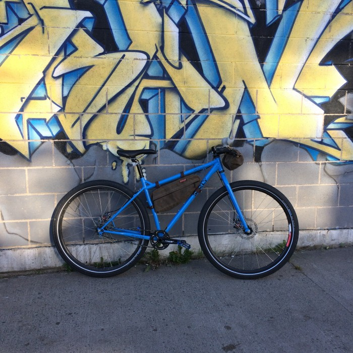 Right side view of a blue Surly bike, parked against a cinder block wall with graffiti