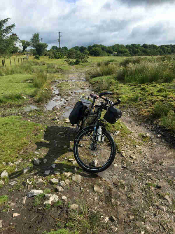 Front view of a Surly Big Dummy bike, parked in a dried up stream bed in a field with trees in the background
