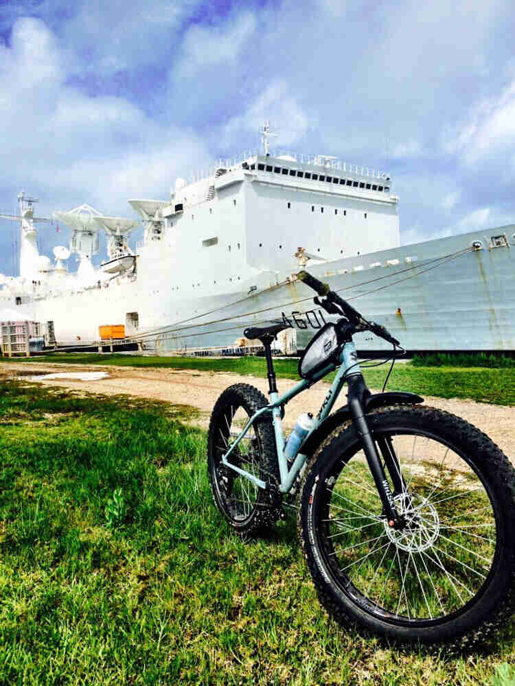 Front left view of a Surly Wednesday MY fat bike parked in grass, next to a gravel road, with a ship in the background