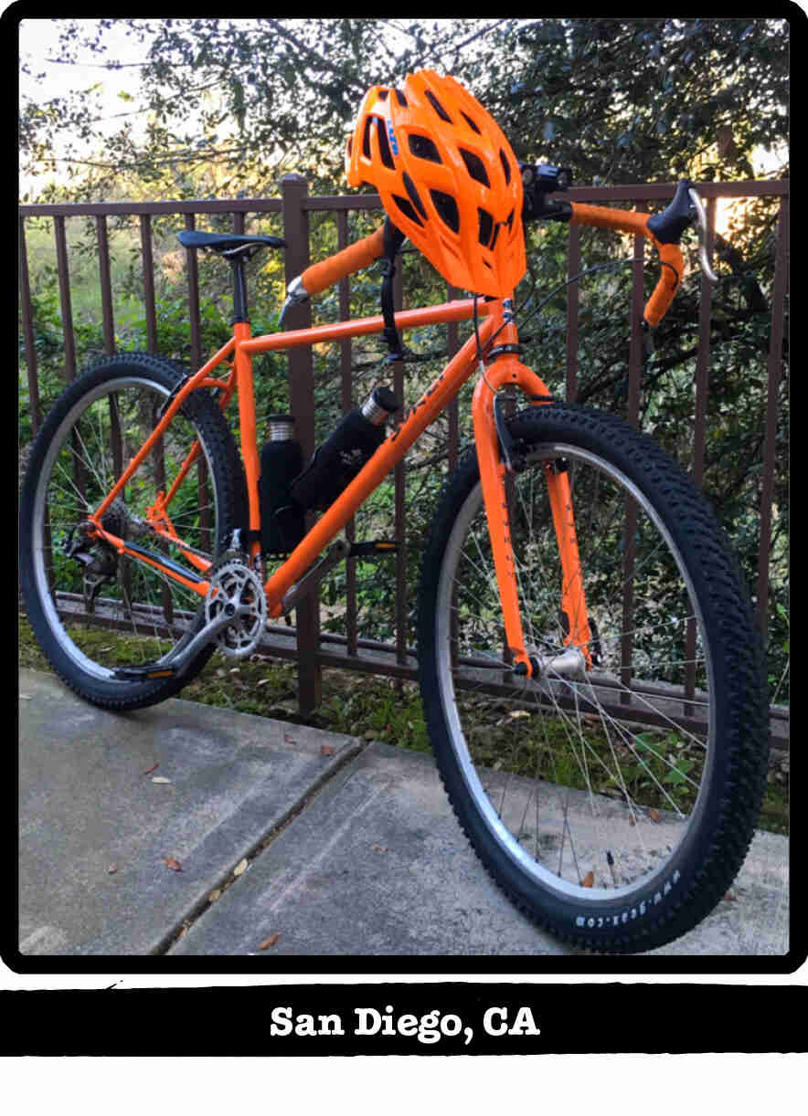 Right side view of a Surly Karate Monkey bike, orange, leaning on a metal rail - San Diego, CA tag below image