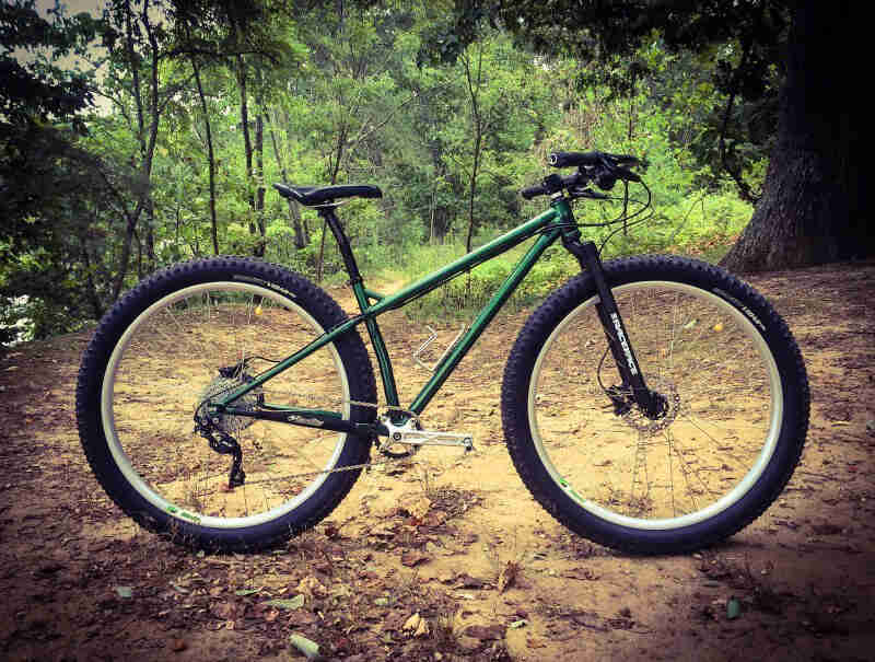 Right side view of a Surly Krampus bike, green, parked on a dirt lot, with a thick forest in the background