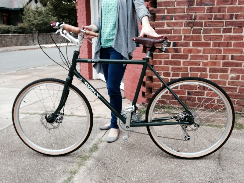 Left side view of a green Surly Disc Trucker bike with a cyclist standing behind, on a sidewalk