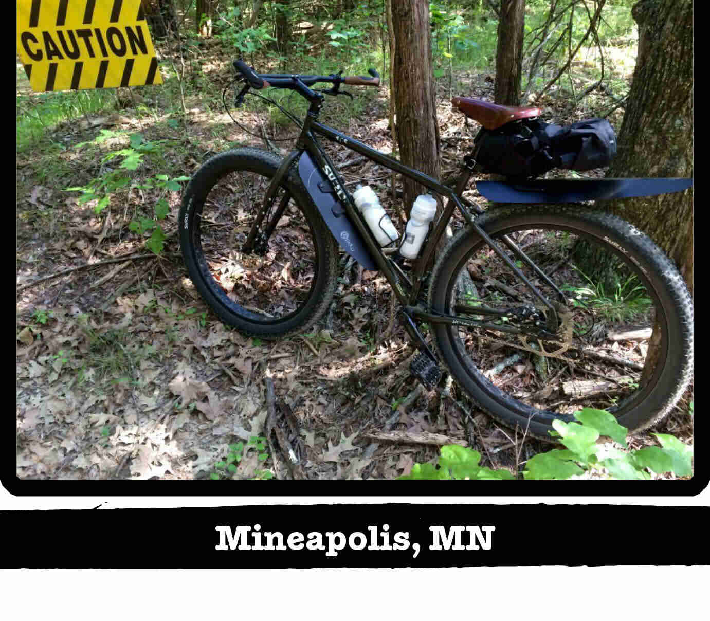 Left side view of a Surly ECR bike, olive, in the woods with a caution sign - Minneapolis, MN tag below image