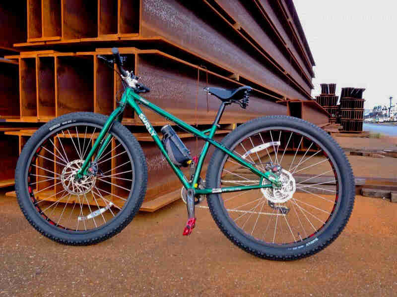 Left side view of a Surly Krampus bike, green, leaning on a stack of beams at a steel yard