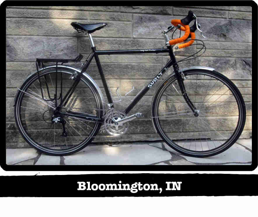 Right side view of a black Surly Long Haul Trucker bike, in front of a stone wall - Bloomington, IN tag below image