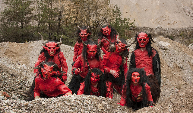 Front view of a group of people, dressed in red Krampus monster costumes, posing together in a small rock pit