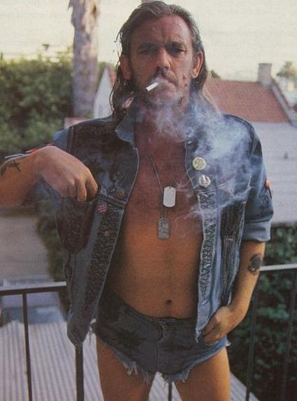 Front view of Lemmy of the band Motorhead, wearing short jean shorts and jean jacket, dog tags while smoking a cigarette