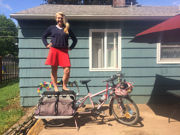 Madi Carlson standing with hands on hips, on the back rack of a Surly Big Dummy bike, custom painted in pink