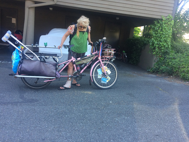 Cyclist with a right broken foot, looks down at a Surly Big dummy bike, pink with a crutch on the rear rack, in front of a garage