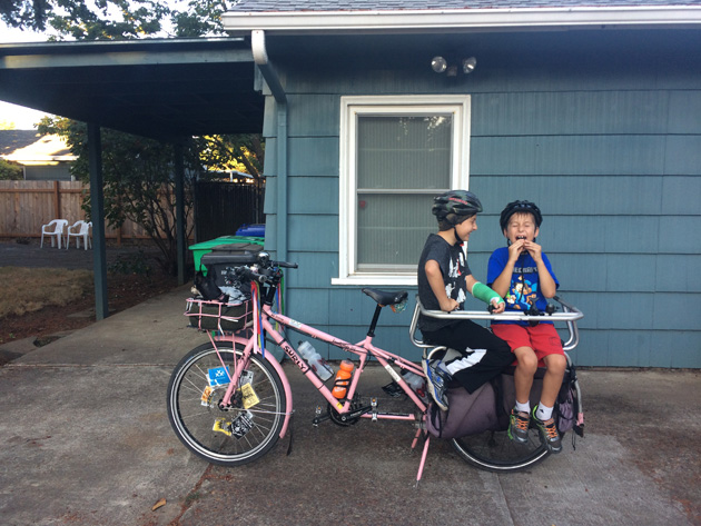 Left side view of a Surly Big Dummy bike, pink, with two children sitting in the rear rack  in front of a house