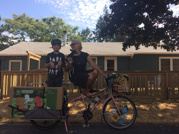 Person seat on a Surly Big Dummy bike, pink, with a child standing up in the rear rack  and house shown in background