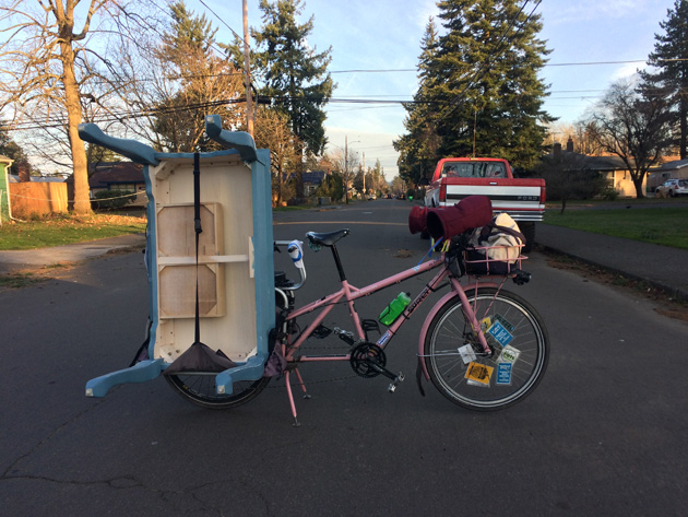 Right side view of a Surly Big Dummy bike, pink, with a blue table on the rear rack, on a street