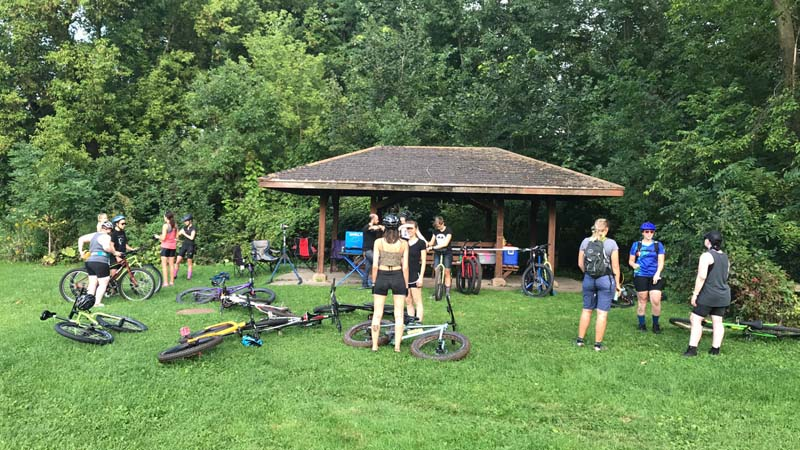 Group of cyclists with their bikes, standing in a grassy field, in and around a gazebo with trees behind it