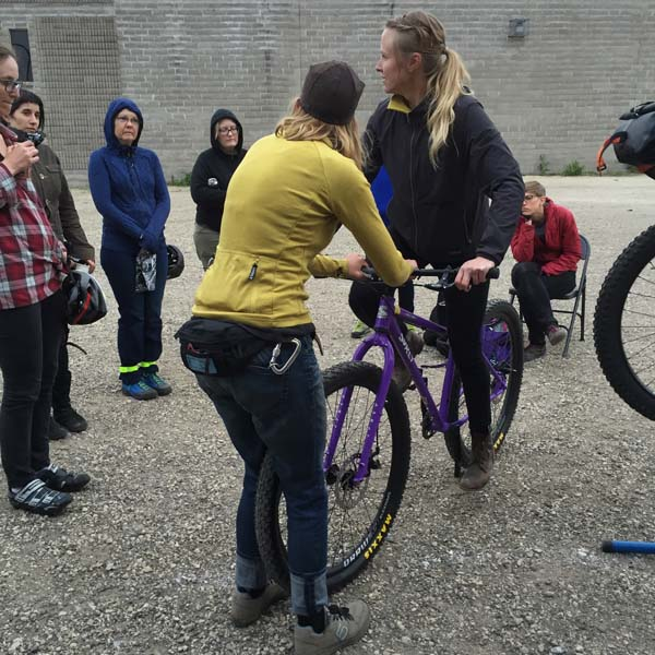 Backside view of a person holding the handlebar of a purple Surly bike with rider, in a gravel lot, with people watching