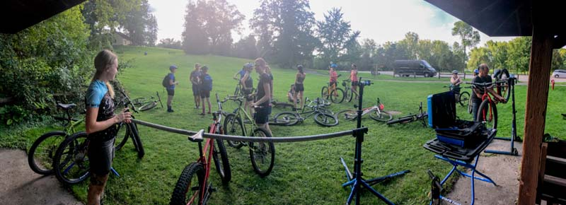 Panoramic view of a group of cyclists standing in a grassy field, with their bikes scattered around, near a park gazebo