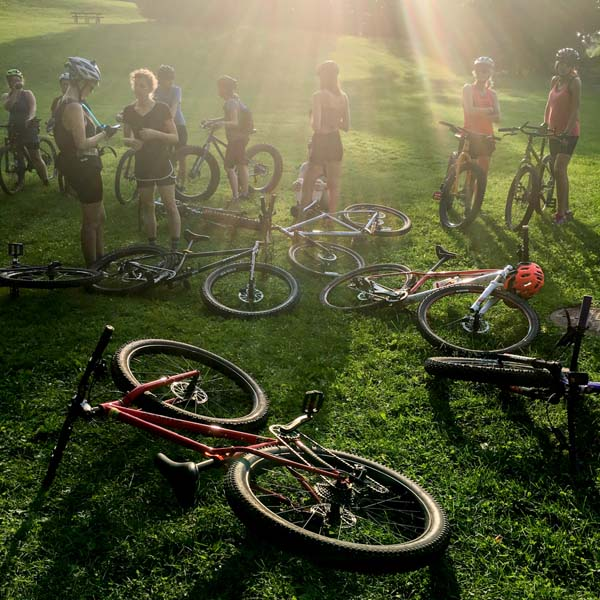 A group of cyclists standing in a grassy field, with their bikes laying around, and a ray of sun shining down on them