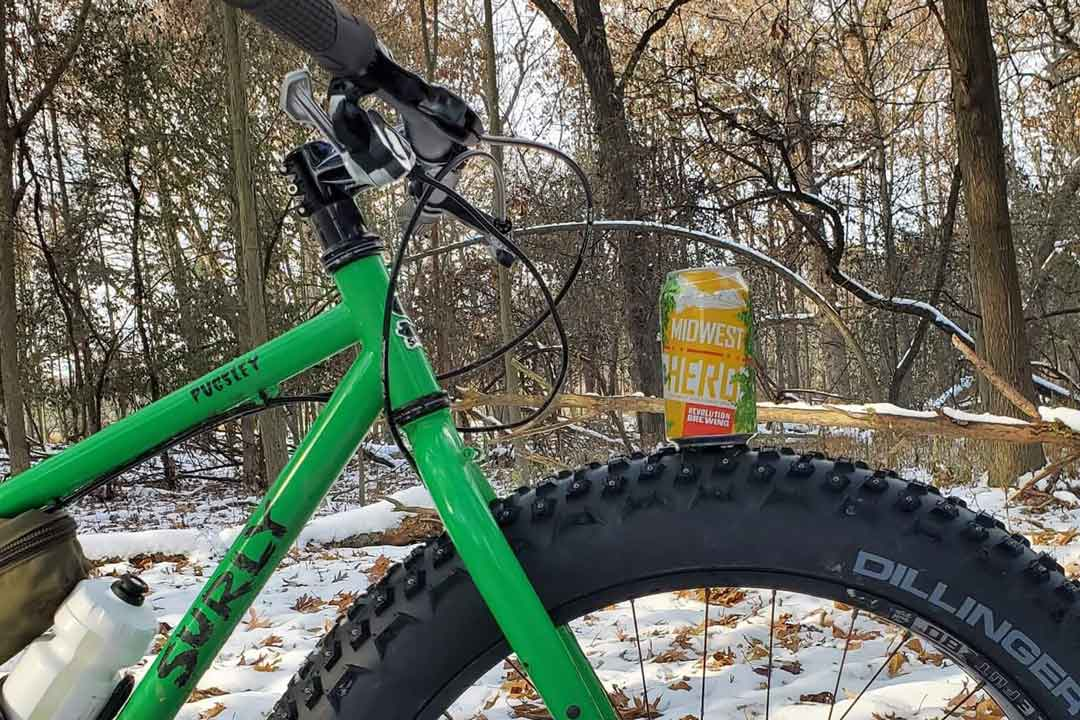 Cropped right profile of the front of a green Surly Pugsley fat bike with beer can on the front tire in the snowy woods