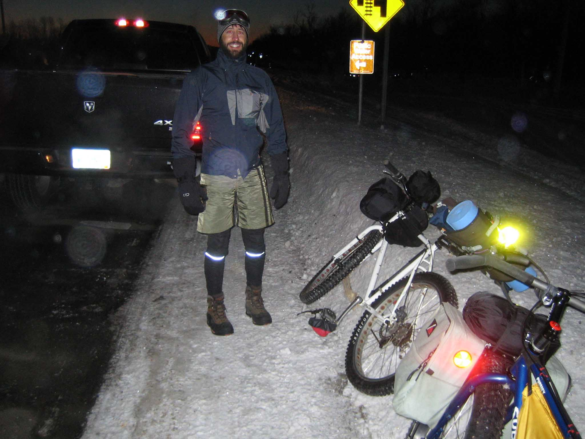 A smiling cyclist standing on a snowy roadside with 2 bikes laying down, at night