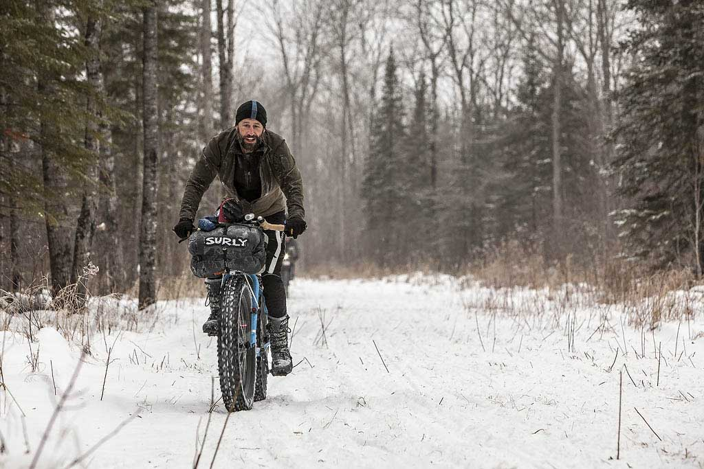 Front view of a cyclist riding a fat bike with a Surly front pack, on a snow covered trail in the woods
