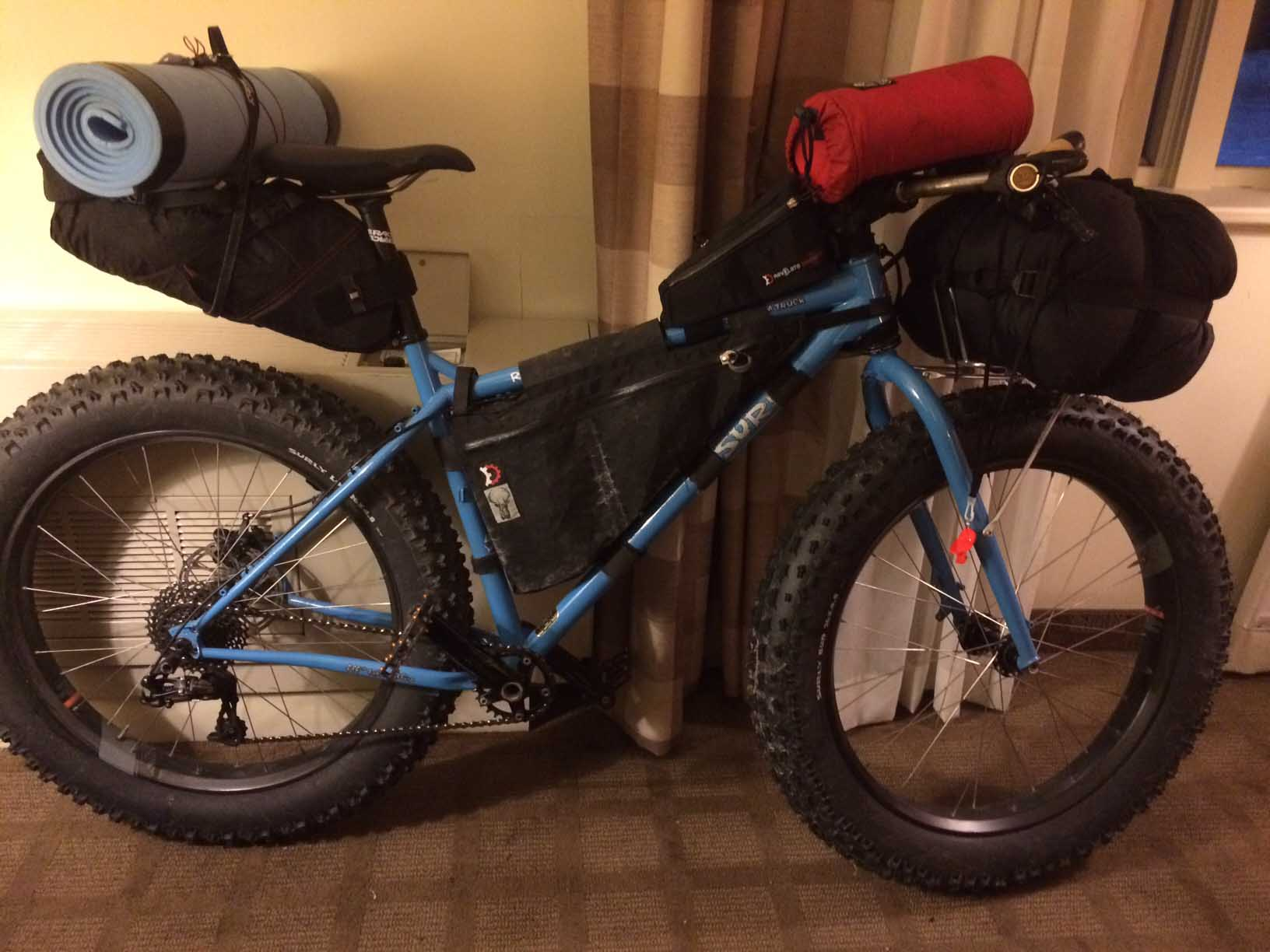Right side view of a blue Surly Ice Cream Truck fat bike loaded with gear, against a room, against the wall