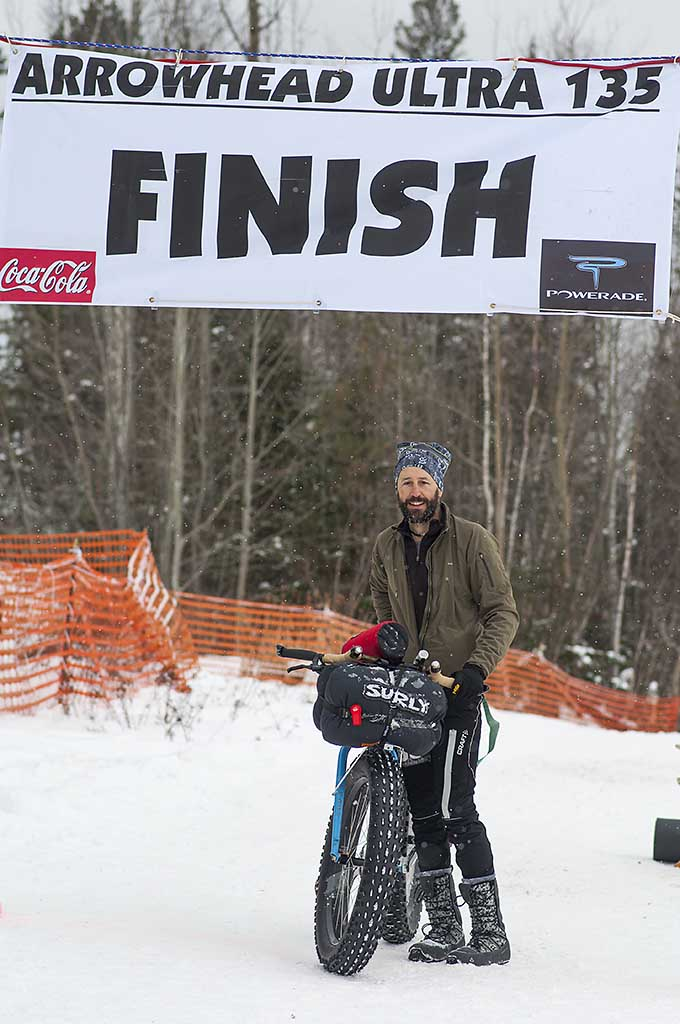 Front view of a cyclist standing next to a blue fat bike with a Surly front pack, at a snowy finish line