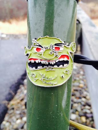 Front, close up view of the head tube of a green Surly Ogre bike, with an ogre emblem attached to it