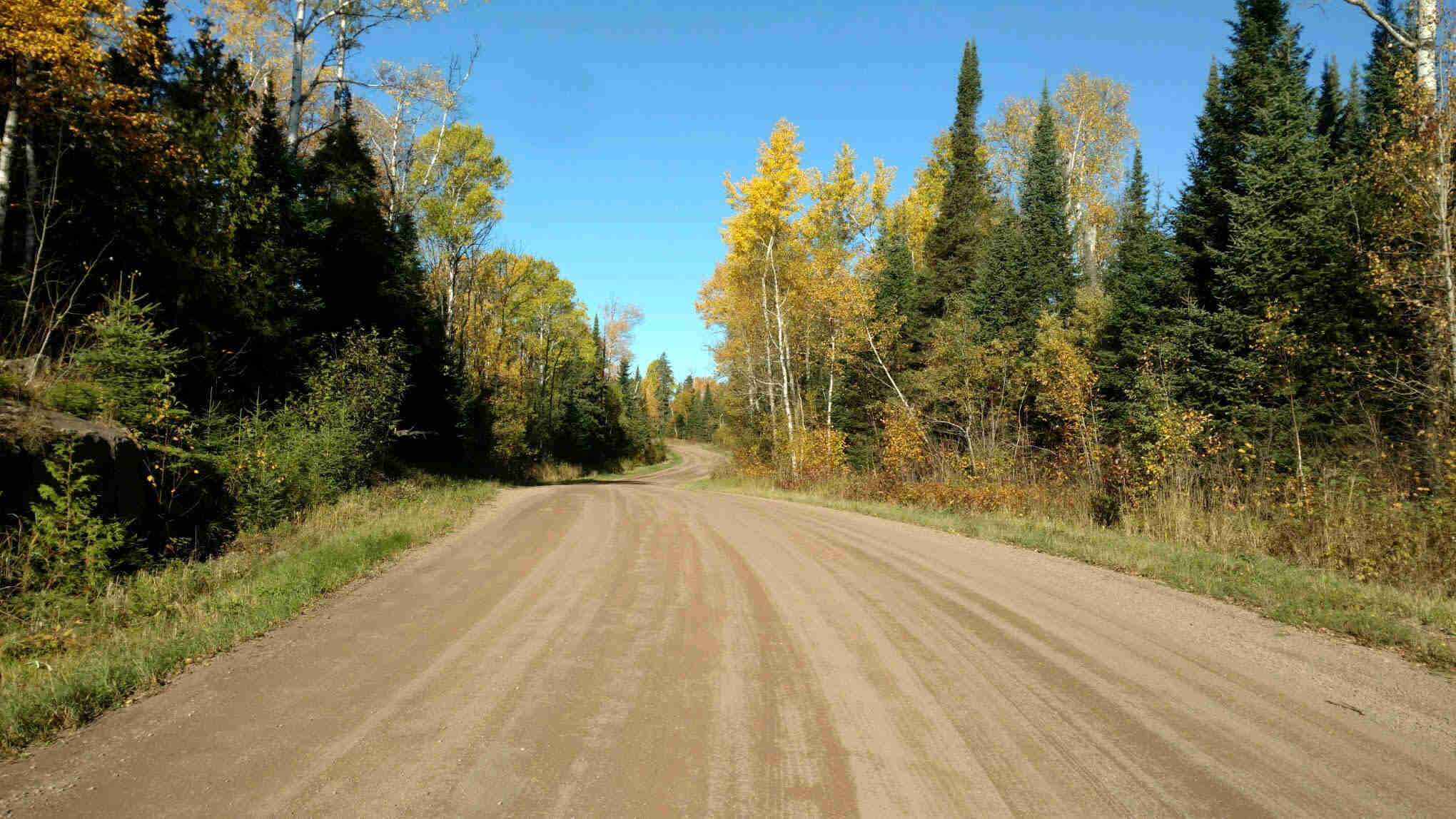 View facing down a wide gravel road with trees on the sides