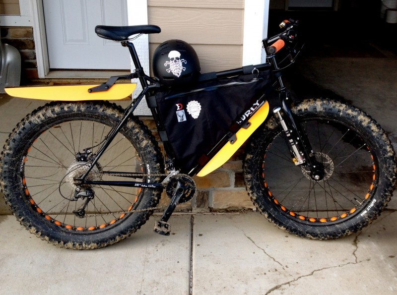 Right side view of a black Surly fat bike with a frame bag, on a walkway, leaning on a wall next to an open garage