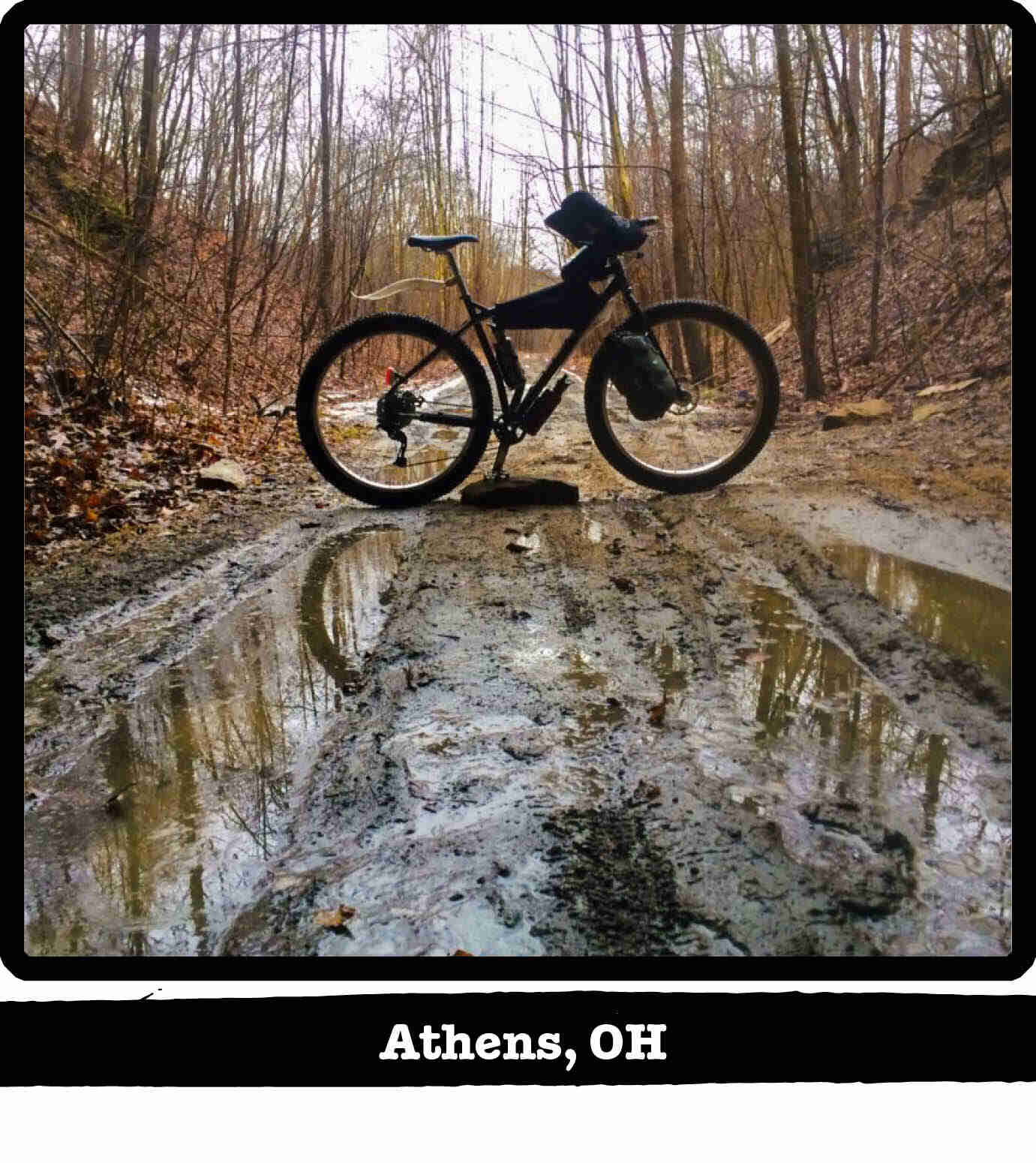 Right profile of a Surly ECR bike standing across a muddy trail in the woods - Athens, OH tag below image