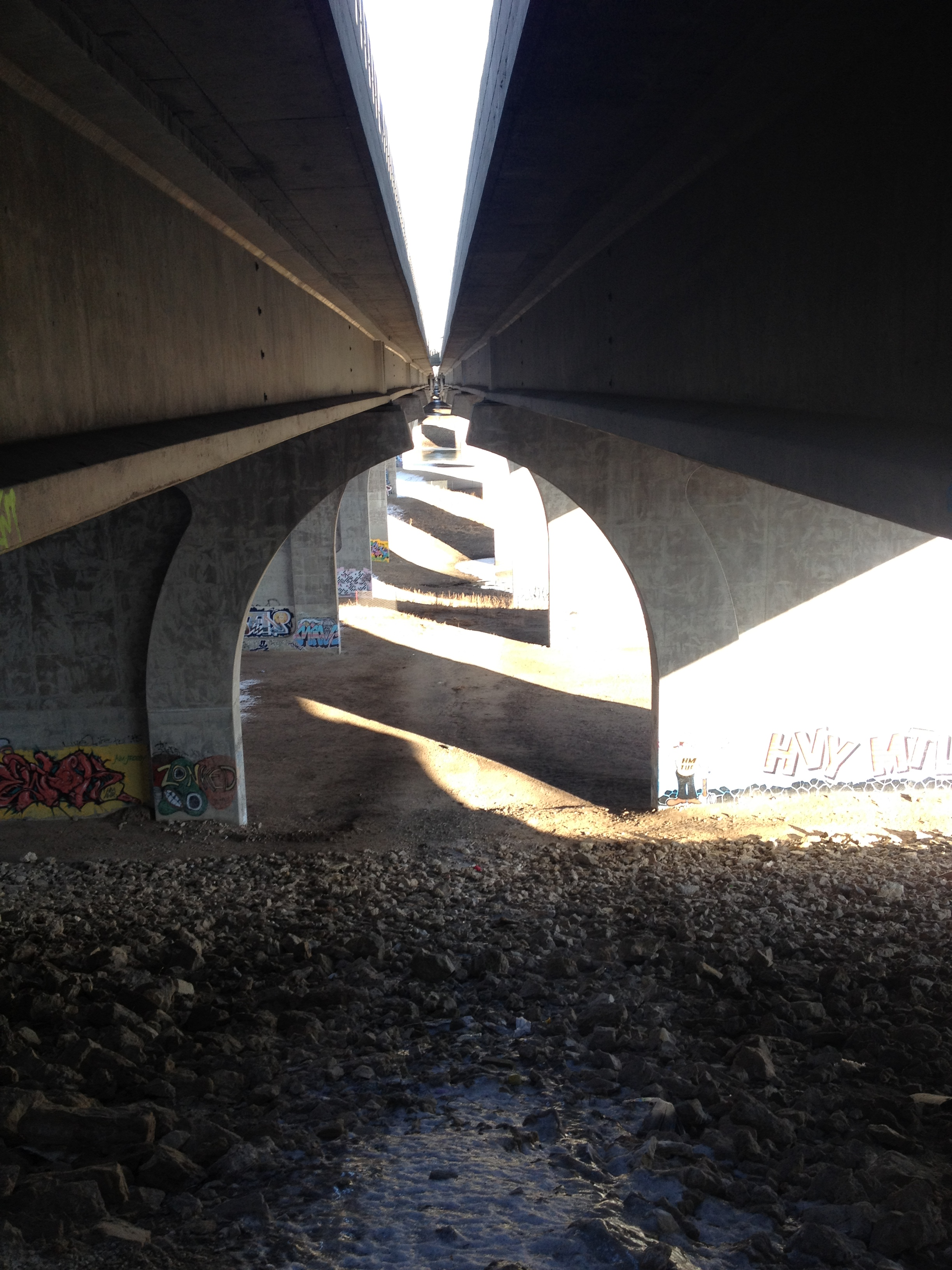 A downward view from between the decks of 2 concrete bridge overpasses that are facing straight away