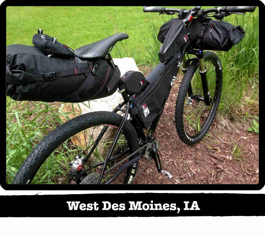 Right side rear view of a Surly Karate Monkey bike with gear, black, in tall grass - West Des Moines, IA tag below image