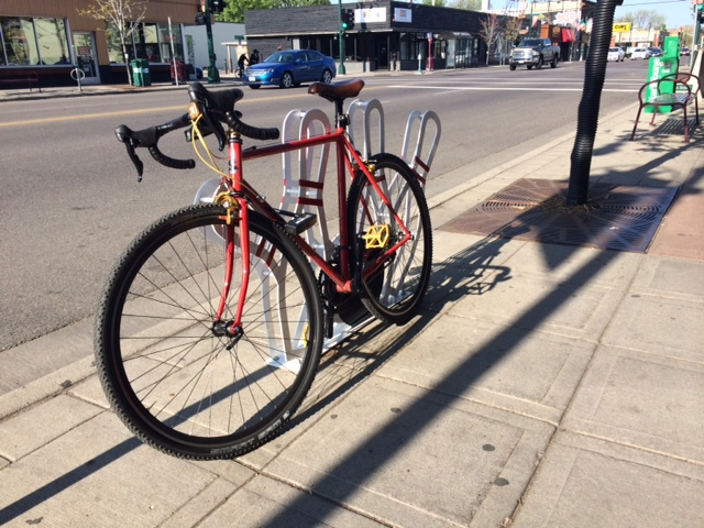 Front, left side view of a red Surly Pacer bike, leaning along a bike rack on a sidewalk with a street behind