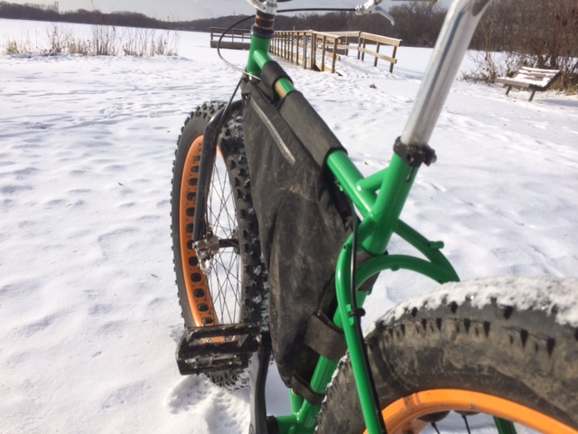 Rear, right side view of a green Surly fat bike, on a snow covered field, facing a wood dock on a frozen lake