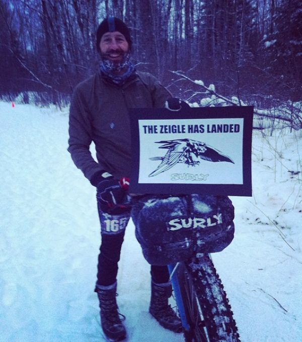 A cyclist standing in snow, next to a fat bike with a Surly front bag, holding a The Zeigle has landed sign