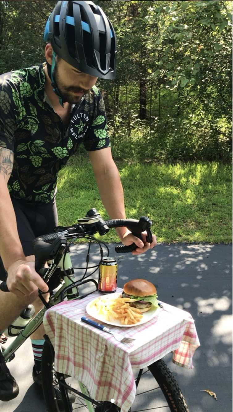 A cyclist standing over a Surly bike on a paved trail with trees, looks down at a plate of food on the bike's gear rack