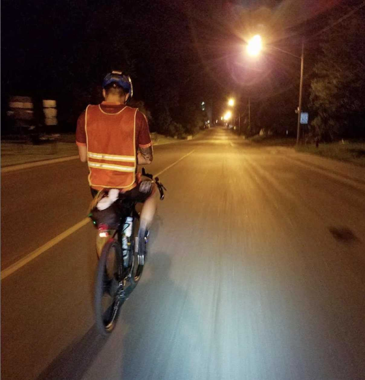 Cyclist wears a reflective vest while riding a bike down a city street at night under the street lights