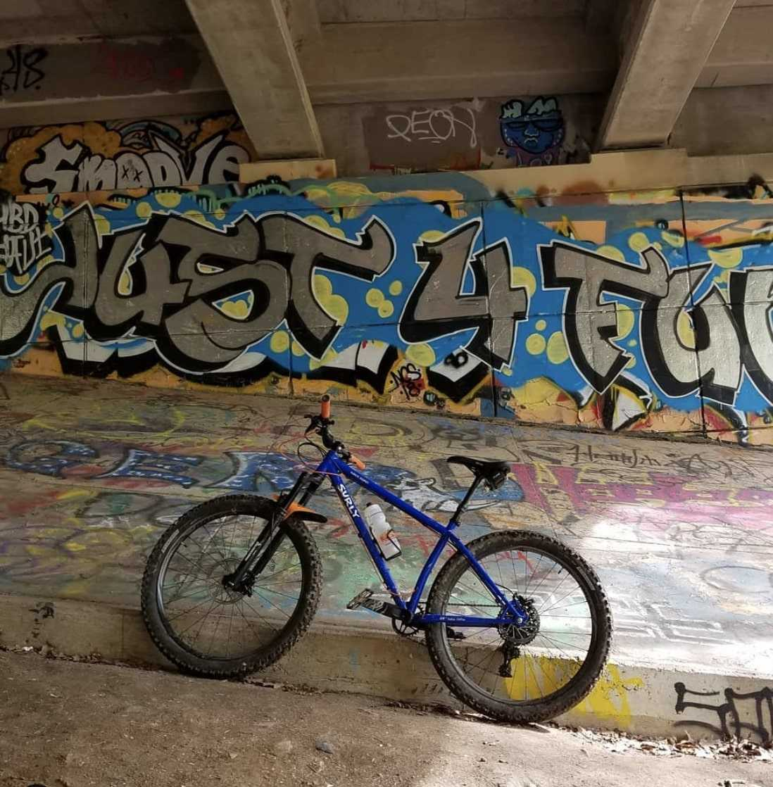 Left side profile view of a blue Surly Karate Monkey bike facing uphill under a graffiti clad concrete bridge