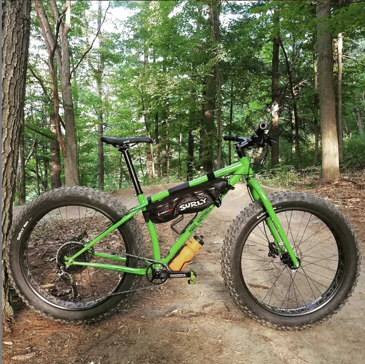 Right side profile view of a green Surly Ice Cream Truck fat bike with gear set on a dirt trail in the pine trees