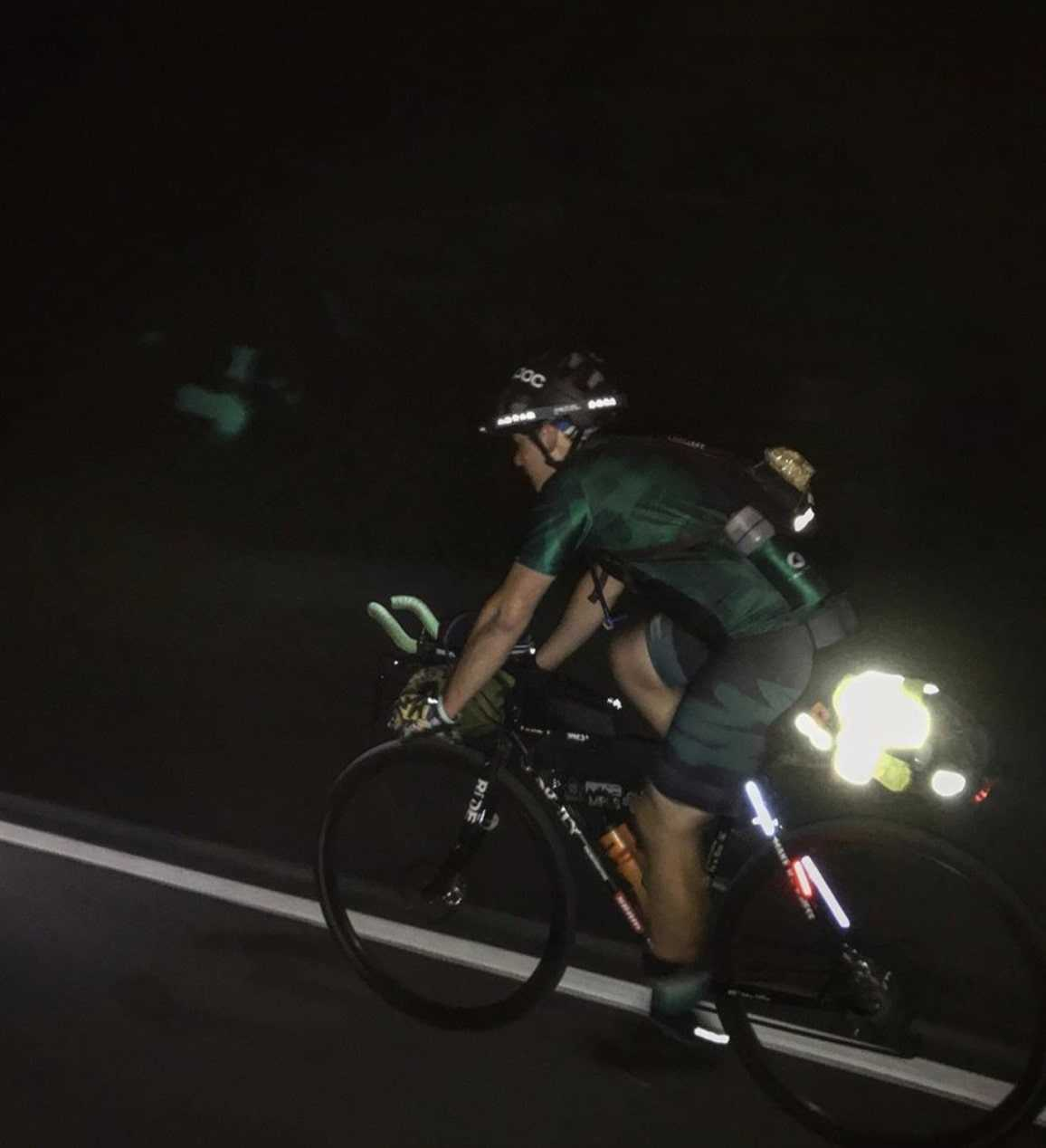 Left side view of a cyclist riding a bike with a reflective rear gear bag pedals in the dark down a paved roadway