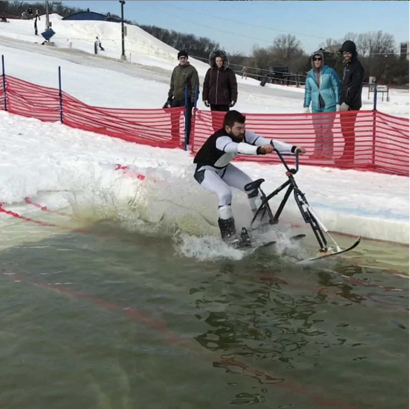 Person rides a bike with skis over a water hole in the snow at ski hill with spectators and a snow fence in background