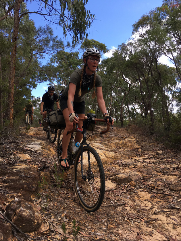 Cyclist rides a down rocky trail hill in the trees with 2 riders trailing behind