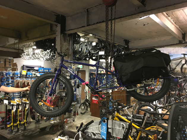 A Surly Big Fat Dummy bike, blue, hanging from a ceiling on two chain hoists in a bike shop