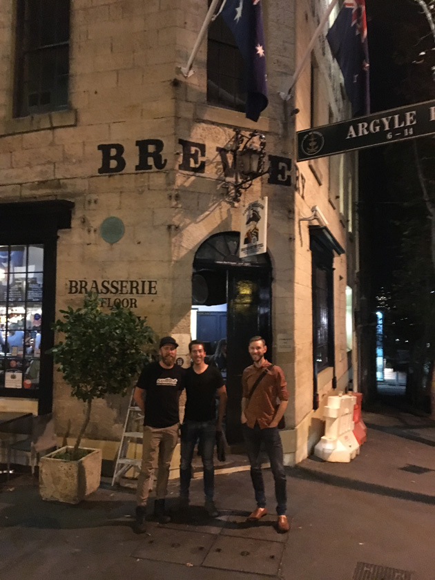 Three friends stand posing in the front corner of a stone brick brewery building at night