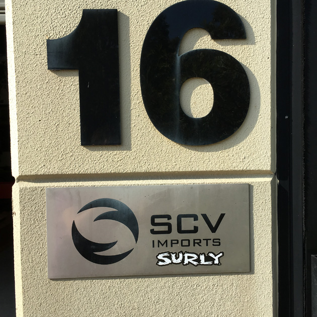 Tan wall with the number 16, black, with an SCV Imports Surly sign mounted below